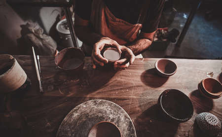 Closeup photoshoot of working process with clay by diligent man.