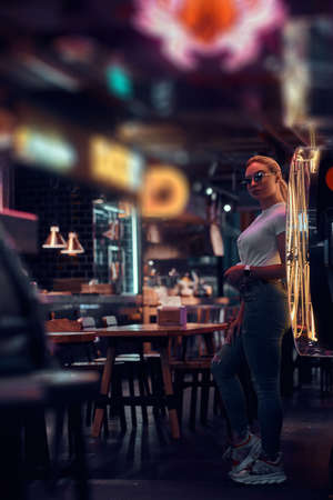 Attractive young woman in sunglasses at neon bar is posing for photographer.