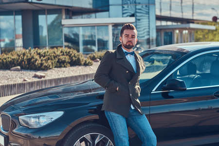 Groomed attractive man is leaning on his own car on the parking. Standard-Bild