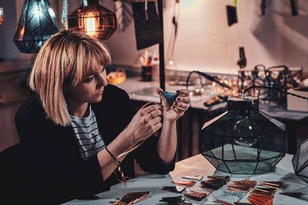Mujer talentosa está trabajando en su nuevo proyecto de lámpara en el estudio de lámparas artesanales.