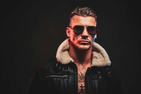 Portrait of a stylish man in jeans jacket with dark glasses and stylish hair on a dark background. Stock Photo
