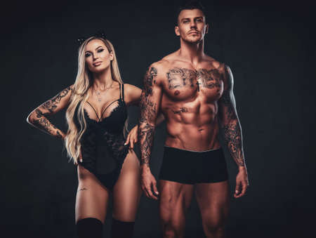 Beautiful couple, handsome tattooed male and alluring girl in black underwear, posing in studio.