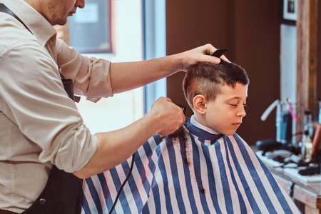Small pretty school boy had his first trendy haircut at modern barbershop.