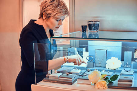 Elegant store assistant put new ornamentations variety of beautiful jewel on display with flowers in jewellery shop. Banque d'images - 123966796