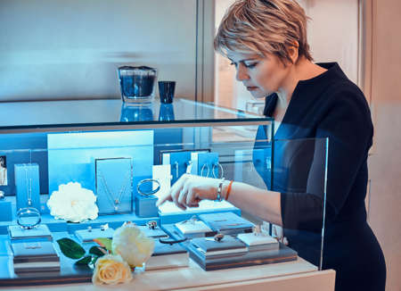 Elegant store assistant put new ornamentations variety of beautiful jewel on display with flowers in jewellery shop. Banque d'images - 123966798