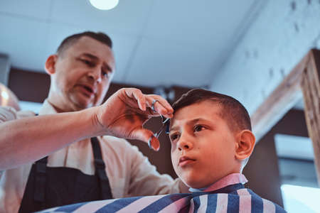 Attractive school boy is getting trendy haircut from mature hairdresser at fashionable hairdressing salon.