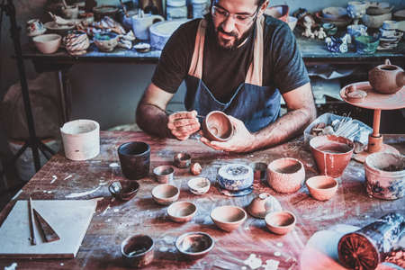 Pensive entusiastici potter in glasses at his  own workshop is workig on a new handmade teapot. Stock fotó