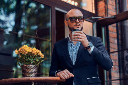 Cheerful groomed gentelman in sunglasses is enjoying his coffeebreak with cup of fresh latte.