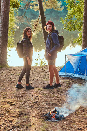 Two young students are going for a walk from forestal campsite. They are standing near tent and bonfire. There are river nearby. Banco de Imagens