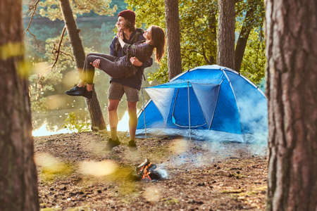 Young romantic couple have fun in summer forest near their tent. Man is holding woman, she hug him.