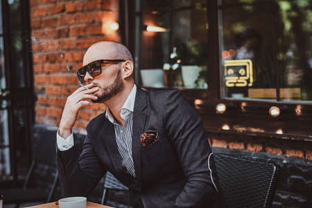 Pensive modern man is smoking a cigarette outside of coffeshop while drinking his cup of coffee. Stock Photo