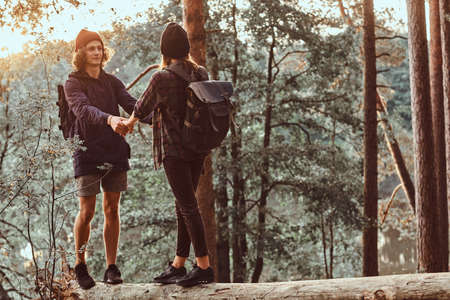 Romantic happy hikers are watching sunset in green lush forest. They have hats and backpacks. 写真素材