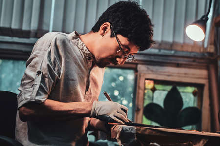 Expirienced diligent restorer is working on antique stained glass restoration at his own workshop. Imagens