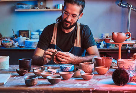 Pensive progressive potter in glasses at his  own workshop is workig on a new handmade teapot.