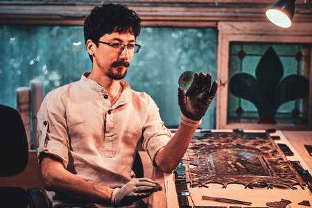 Expirienced restorer is choosing right peace of stained glass for his project at his workplace.