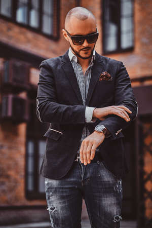 Handsome man in dark blaser and sunglasses is checkin what time is now. Stock Photo