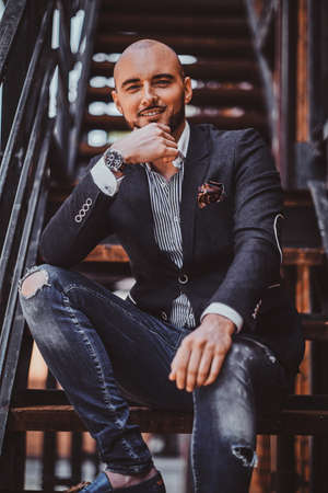 Portrait of smiling attractive man in blazer and ripped jeans which is sitting on the stairs.