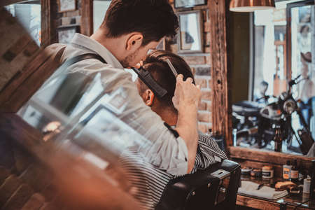 Thendy focused hairdresser at modern barbershop is working on clients haircut. Banco de Imagens - 124964743