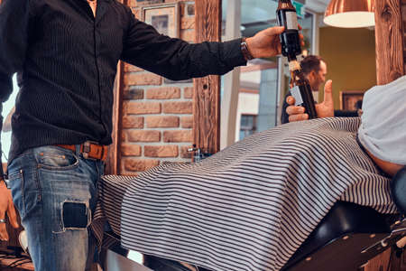 Two friends at trendy modern barbershop are celebraiting new beard cut with drinks.