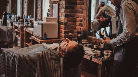 Attractive brutal man just got good beardcare from talanted trendy barber.