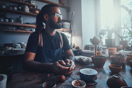 Talented pensive artist at his own pottery studio is workig for new project.