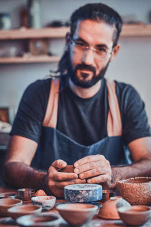 Diligent pensive man in glasses at his  pottery workshop is workig for new project. Stock fotó