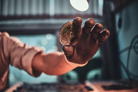 Closeup photo shoot of mans hand holding peace of restorer glass. Banco de Imagens