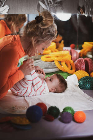 Cheerful pediatrician doing special physical activity for pretty toddler at her cozy cabinet with toys.