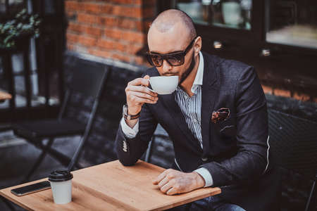 Pensive groomed man is enjoying coffee while sitting outside at cafe on his own break.