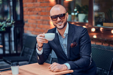 Elegant smiling man is drinking coffee while sitting outside at cafe on his break.