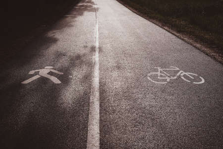 Asphalt road, divided for two parts - one part for cyclists, other for pedastrians.