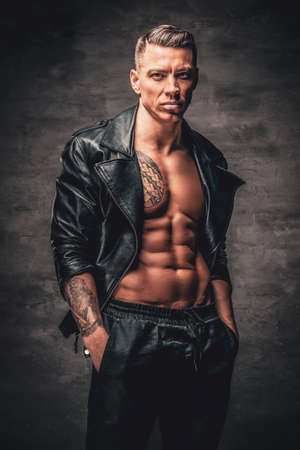 Studio portrait of handsome male with tattoo on a chest, dressed in a black leather jacket.