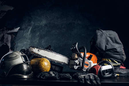 Safety unform on the table -  boots, helmet and gloves with oxygen cylinder, respirator and chainsaw. There are dark background. Banco de Imagens
