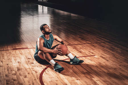 Portrait of Black basketball playersits on a floor in a basketball hall. Stock Photo