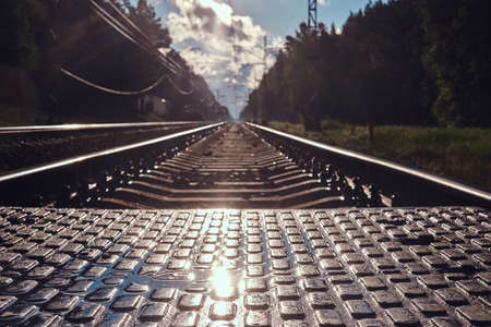 Low angle photo of rails and sleepers and pedastrin transition in sunshining summer day.
