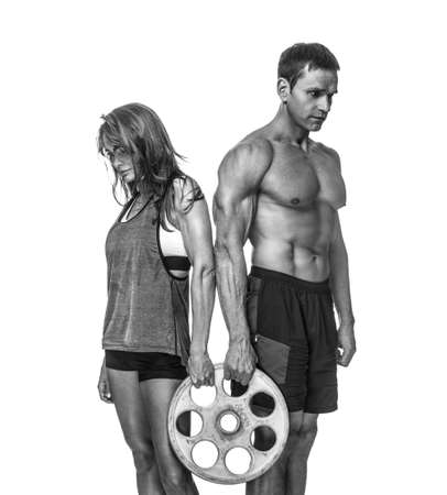 Shirtless middle age sporty male and slim female holds barbell weight.