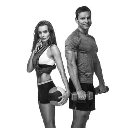 Sporty couple with dumbbells and ball isolated on a white background.