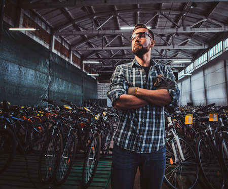 Pensive man in protective glasses and checkered shirt is posing at his own warehouse full of bicycles. Imagens