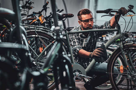 Busy attractive man in protective glasses is cleaning one of bicycle from dust.