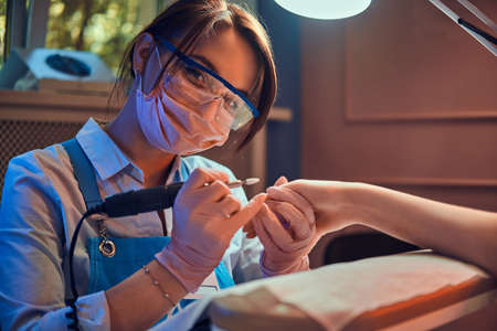 Young cheerful manicurist in glasses and protective mask is working at her workplace with customer.