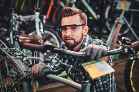 Happy attractive man in protective glasses and shirt is checkin bicycles chain for customer. Imagens