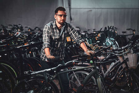 Diligent hardworking man in checkered shirt is working with bicycles at busy warehouse.