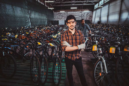 Attractive pensive mam in glasses is posing next to bicycles at his own warehouse. Imagens
