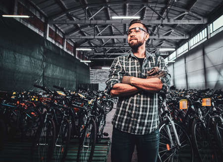 Pensive handsome man crossed his hands is posing at mountain bycicles warehouse.
