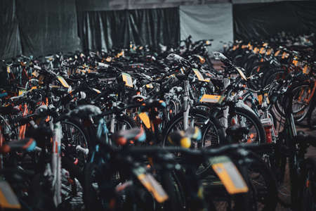 A lot of different bicycles at busy warehouse are ready to go.