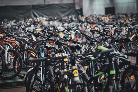 A lot of new bicycles are standing at warehouse waiting for customers.
