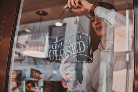 Man in white shirt is putting nameplate about closing at his own shop. Stock Photo