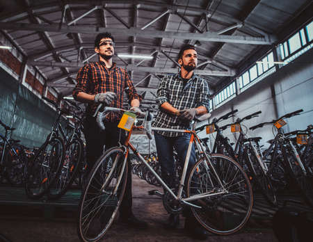 Two attractive workers are posing with his bicycles at bicycle warehouse. Mans are wearing checkered shirts. Imagens