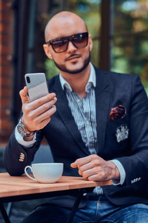 Attractive elegant businesman in sunglasses is sitting in cafe outside while chatting on mobile phone.