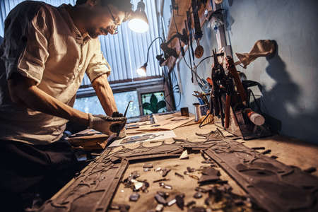 Diligent craftman is restoring ancient broken stained glass at his own workshop. 写真素材 - 124975993